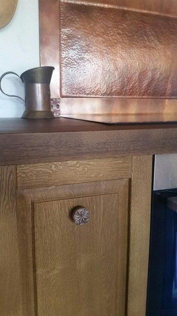 Gałki kuchenne z repusowanej miedzi na tle miedzianych elementów kuchni