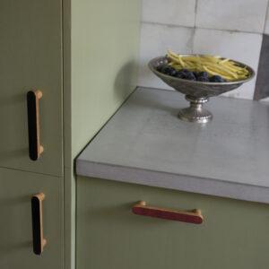 Uchwyty podłużne i gałki emaliowane w szaro-zielonej kuchni